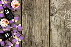 Halloween candy border against rustic wood. Halloween candy side border against a rustic wood background Royalty Free Stock Photos