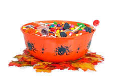 Halloween candy in a bowl with fall leaves. Closeup halloween candy in a bowl with fall leaves stock photography