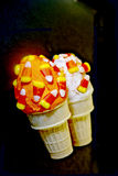 Halloween candy corn cupcake cones. Two yummy halloween ice cream cone cupcakes topped with buttercream frosting and candy corn on a black background Stock Photography