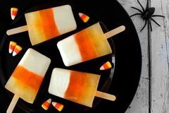 Halloween candy corn ice pops on black plate Royalty Free Stock Photo