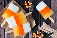 Halloween candy corn ice pops on rustic wood background Stock Images