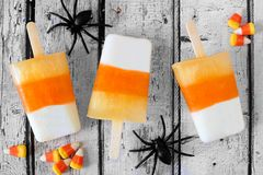 Halloween candy corn popsicles downward view on white wood background. Halloween candy corn popsicles downward view on rustic white wood background with toy royalty free stock images