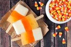 Halloween candy corn popsicles on rustic wood background Royalty Free Stock Photo