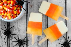 Halloween candy corn popsicles on white wood background. Halloween candy corn popsicles downward view on old white wood background with toy spiders stock image
