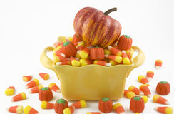 Halloween Candy Corn and Pumpkin. Halloween Candy Corn in a yellow candy dish with a little pumpkin on top, horizontal with copy space, isolated on white stock photos
