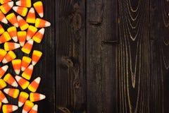 Halloween candy corn side border on dark wood. Halloween candy corn side border on an old dark wood background Stock Photos