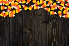 Halloween candy corn top border on dark wood Stock Images