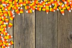 Halloween candy corn top corner border over old wood Stock Photo