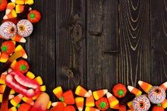 Halloween candy corner border over dark wood. Halloween candy corner border over a dark black wood background Stock Photos