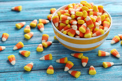Halloween candy corns. In bowl on blue wooden background stock photo