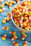 Halloween candy corns. In bowl on blue wooden background stock image