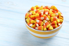 Halloween candy corns. In bowl on blue wooden background royalty free stock photos