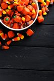Halloween candy corns. In bowl on black wooden background royalty free stock image