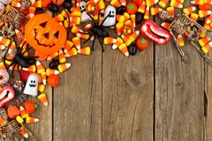 Halloween candy and decor top corner border over rustic wood Royalty Free Stock Photography
