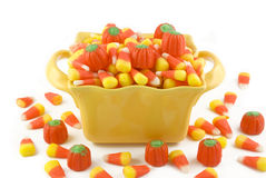 Halloween Candy In A Dish. A yellow dish filled with Halloween candy corn and candy pumpkins, isolated on white background with copy space stock photo