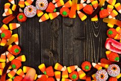 Halloween candy frame over dark wood. Halloween candy frame over a dark black wood background Royalty Free Stock Images