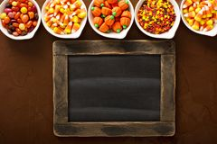 Halloween candy in little white bowls. Assorted Halloween candy in little white bowls with a chalk board stock image