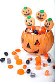 Halloween candy in pumpkin bowl. Halloween candy scattered around and in a pumpkin shaped bowl royalty free stock image