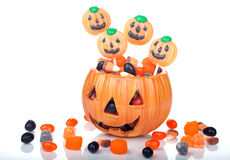 Halloween candy in pumpkin bowl. Halloween candy scattered around and in a pumpkin shaped bowl stock images