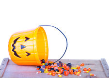 Halloween candy and pumpkin bucket on wood Stock Images