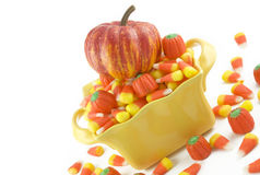 Halloween Candy with Pumpkini. A yellow bowl full of Halloween candy, candy corn, and candy pumpkins, diagonal viewpoint, with pumpkin on top of candy royalty free stock images