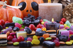 Halloween Candy with pumpkins on dark wood background. Stock Photo