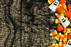 Halloween candy side border against spooky black background. Halloween candy side border against a rustic wood and black cloth background Royalty Free Stock Image