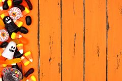 Halloween candy side border over old orange wood. Halloween candy side border over an old orange wood background Stock Photography
