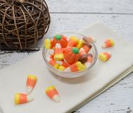 Halloween Candy. Tasty candy corn in a glass bowl on napkin. Copy space. Halloween scene royalty free stock photography