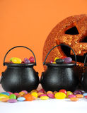 Halloween candy in trick or treat carry cauldrons with pumpkin - vertical closeup. Royalty Free Stock Photos