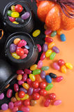 Halloween candy in trick or treat carry cauldrons - vertical closeup. Happy Halloween candy in trick or treat carry cauldrons with witches hat on orange Royalty Free Stock Photos