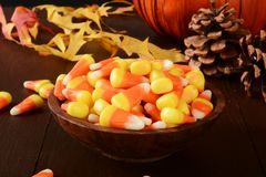 Halloween candy. A wooden bowl of candy corn on a halloween table with a decorative pumpkin stock image