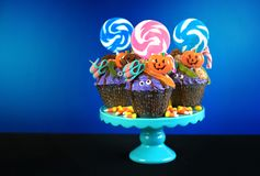 Halloween candyland drip cake style cupcakes with candy on blue background. Royalty Free Stock Images