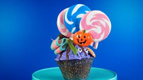 Halloween candyland drip cake style cupcakes with candy on blue background. Royalty Free Stock Photography