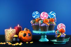 Halloween candyland drip cake style cupcakes with candy on blue background. Stock Image