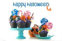 Halloween candyland drip cake style cupcakes with lollipops and candy on white. Royalty Free Stock Photos