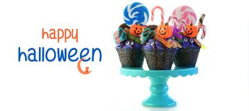 Halloween candyland drip cake style cupcakes with lollipops and candy on white. Royalty Free Stock Photography