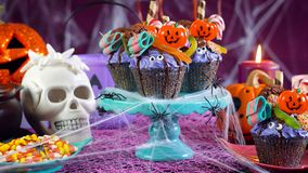 Halloween candyland drip cake style cupcakes in party table setting. Royalty Free Stock Photo