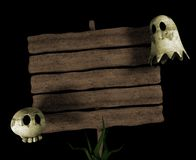 Halloween cartoon signpost. An old wooden road sign with two halloween characters: a skull and a ghost Stock Photography