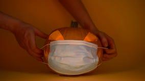 Hands put protective mask on carved halloween pumpkin, coronavirus quarantine