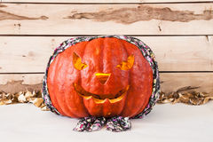 Halloween.  Carved pumpkin in bandana on a wooden background Royalty Free Stock Photography