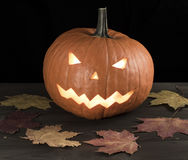 Halloween carved pumpkin, jack-o-lantern on wooden table with leaves Royalty Free Stock Photos