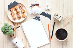 Mock up of open notebook, paper crafts, cube calendar, grilled carrots with scary face and coffee cup Royalty Free Stock Photos