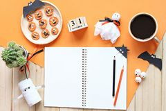 Mock up of open notebook, paper crafts, cube calendar, grilled carrots with scary face and coffee cup Stock Image