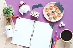 Mock up of open notebook, paper crafts, cube calendar, grilled carrots with scary face and coffee cup Stock Images