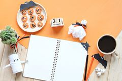 Mock up of open notebook, paper crafts, cube calendar, grilled carrots with scary face and coffee cup Royalty Free Stock Images