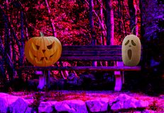 Halloween two scary carved pumpkins on a park bench in a spooky forest landscape. Halloween celebration two scary carved pumpkins on a park bench in a spooky stock illustration