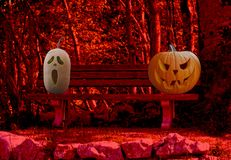 Halloween celebration two scary and spooky carved pumpkins on a park bench in a horror forest landscape royalty free stock photography