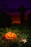 Halloween Cemetery. Halloween jack o lantern in cemetery with cross in background Stock Images