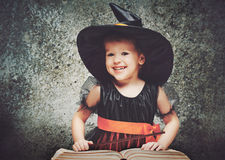 Halloween. cheerful little witch with magic wand and book conjur Stock Photography